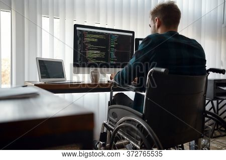 Back View Of Young Caucasian Male Web Developer In A Wheelchair Writing Program Code While Sitting A
