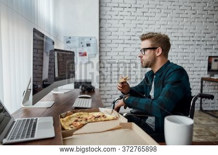 Caucasian Male Web Developer In A Wheelchair Eating Pizza And Looking At Multiple Computer Screens W