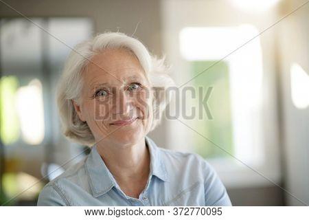 Portrait of smiling senior woman with white hair