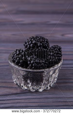 Small Glass Pot Overfilled With Blackberries. Close-up. Grey Wooden Background.