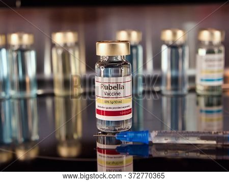 Vial Of Rubella Vaccine With A Syringe On A Stainless Steel Background.