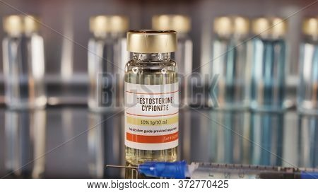 Vial Of Testosterone Cypionate With Syringe On A Stainless Steel Background.