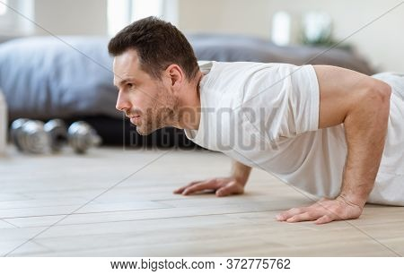 Home Workout. Sporty Man Doing Push-ups Exercise Training Staying Fit Indoor On Weekend.