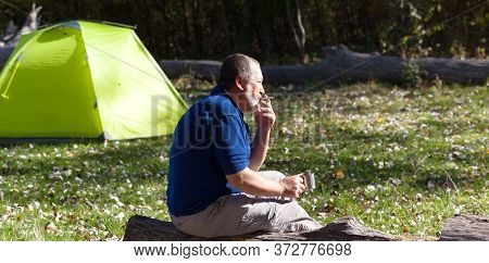 Man Sitting On Wooden Log With Mug Of Tea And Cigarette. Hiker Basks In Sun, Drinks Tea And Smokes C