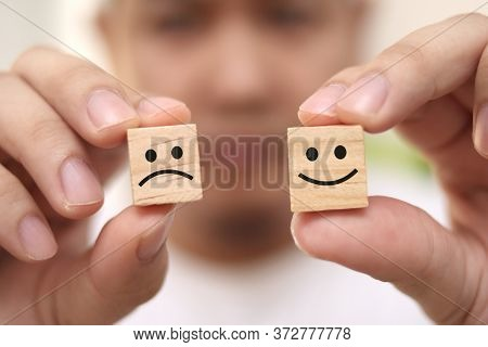 Life Is A Choice, Be Happy Or Sad Concept, Man Holding Wooden Block With Happy And Sad Face Drawn On