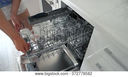 Young Housewife Taking Out Dishes From Dishwasher. Woman Taking Out Glasses And Cups From Dishwasher