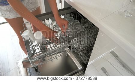 Woman Washing Dishes In Dishwasher. Close Up Shot Of Female Hands Taking Out Clean Glasses From Dish