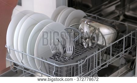 Close Up Open Dishwasher With Clean Plates And Cutlery. Modern Technology For Housewife. How To Load
