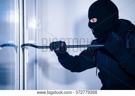 Intrusion Concept. Side View Portrait Of Disguised Prowler Breaking House Or Office Door With Crowba