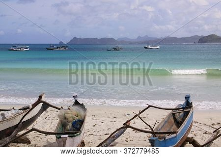 Small Jukung Boats And Breaking Wave In Lombok. Kuta Lombok Is An Exotic Paradise On The Indonesian