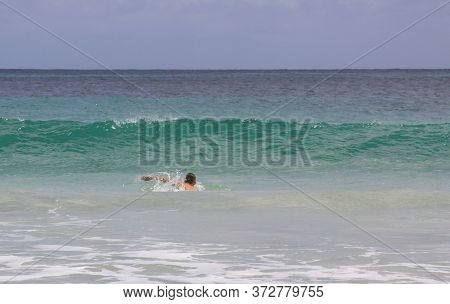 Male Swimmer In Ocean Waves At Mawun Beach Lombok, Indonesia. Kuta Lombok Is An Exotic Paradise On T