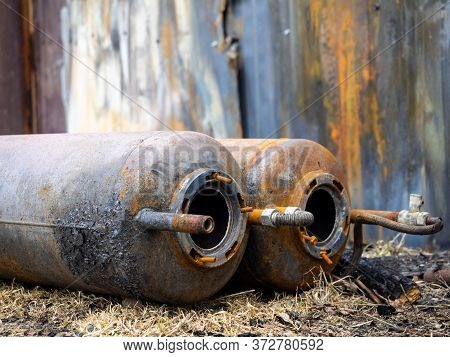 Old Rusty Gas Cylinders Lie On The Ground, Close-up. Dangerous Cylinders As The Cause Of Explosions