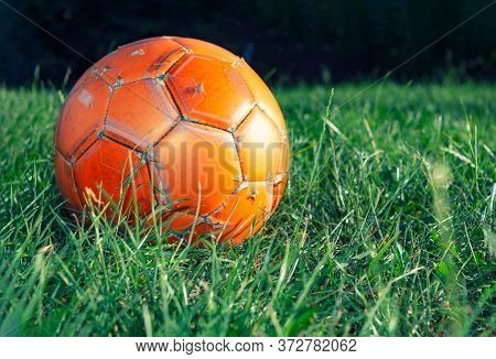 Orange Soccer Ball On Green Grass. The Concept Of Street Football. An Old Ball With Cracks. Healthy