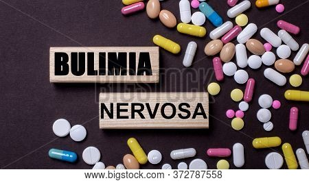 Bulimia Written On Wooden Blocks On A Dark Background Among Multi-colored Pills. Medical Concept