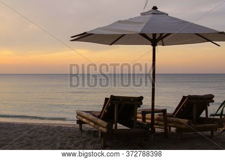 Tropical Umbrella And Bamboo Long Chairs On The Beach With Calm Sea At Sunset, On Gili Air Island, L