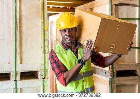 Portrait of african black warehouse worker hold cardboard box packaging on his shoulder in large warehouse distribution center environment. Using in business warehouse and logistic concept.