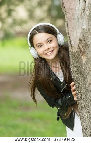 Baby Tech. Happy Child Wear Headphones Outdoors. Small Girl Listen To Music In Headphones. Protectin