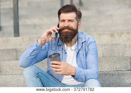 Small Talk With Someone. Happy Hipster Drink Coffee Talking On Phone Outdoors. Making Phone Call. Ce