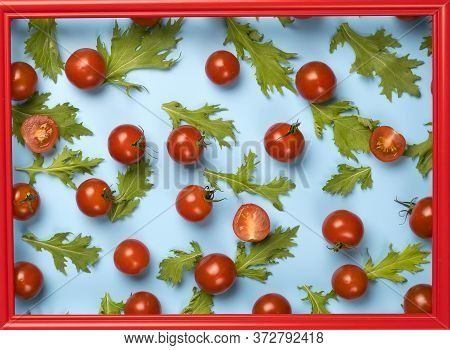 Red Cherry Tomatoes And Green Rucola Salad Leaves On Blue Background.