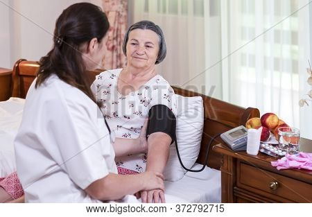 Female Doctor Checking Blood Pressure To Senior Woman At Home Or In Nursing Home. Elderly Healthcare