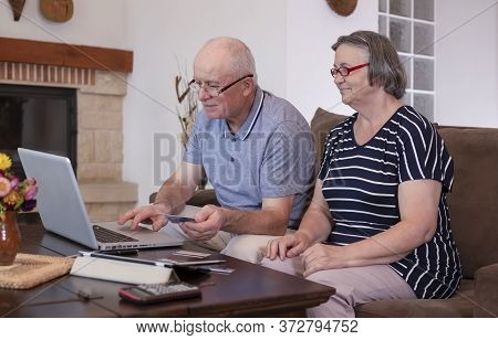 Senior Couple Shopping Online On Laptop Using Credit Card At Home. Internet Banking At Home Concept.