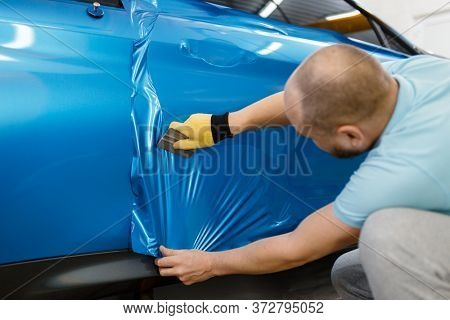 Male mechanic installs protective foil or film