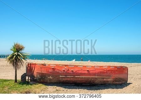Old Red Vessel Boat And Small Palm Tree On Sandy Beach With Blue Sky And Sea Background