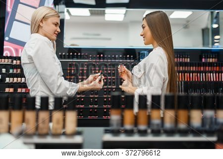Cosmetician helps woman in cosmetics store