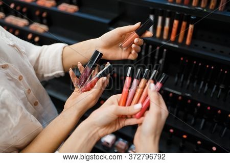 Cosmetician and woman holds nail varnish in store