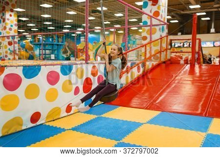 Little girl rides on a swing, entertainment center