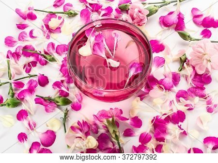Pink Flower Tea With Carnation Petals. Hot Rose Drink In Glass Cup