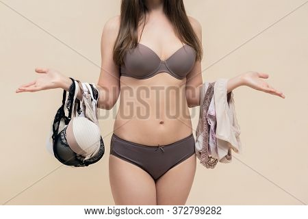 Woman Is Choosing A New Underwear In A Lingerie Store And Is Shrugging Her Shoulders.