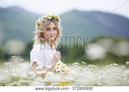 Pretty Young Blonde Woman With Camomiles In White Blooming Field. Girl In Camomile Wreath
