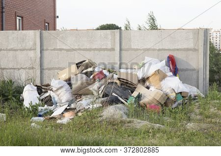 Huge Pile Of Trash In A Field Near Residential Houses