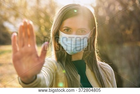 Young Woman Wearing Blue Disposable Single Use Virus Mouth Nose Mask, Hold Hand Front Of Her As Stop