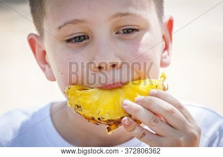 Cute Caucasian Baby Boy Eating Fresh Pineapple Outside In The Summer Heat.