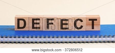 Defect Word Made Of Wooden Blocks With Black Letters, A Row Of Blocks Is Located On A Blue Notepad.