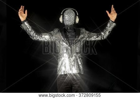 Mr Discoball With Obscured Face And Headphones In Nightclub Dancing Against A Black Background