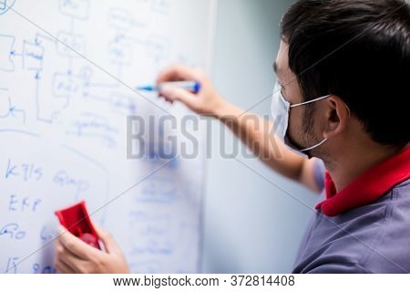 Selective Focus To Business Man Wearing Mask And Writing On White Board In Meeting Room. Asian Man M