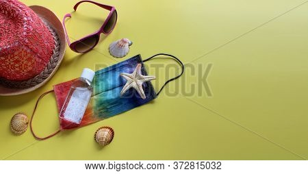 Summer 2020 Concept. Protective Mask Painted In Rainbow Colors, Antiseptic, Beach Hat, Starfish And