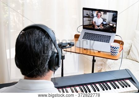 Male Piano Teacher Giving Piano Lessons Online At Home Using A Laptop And Smartphone As Second Camer