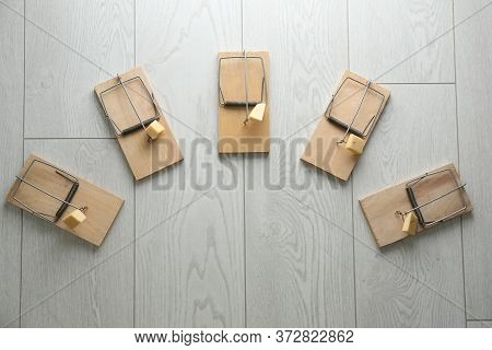 Mousetraps With Pieces Of Cheese And Space For Text On White Wooden Background, Flat Lay. Pest Contr