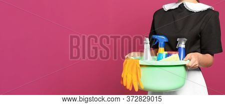 Young Chambermaid Holding Plastic Basin With Detergents On Color Background, Closeup View With Space