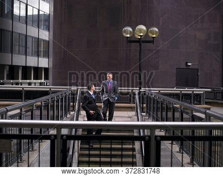 Two business men descending steps