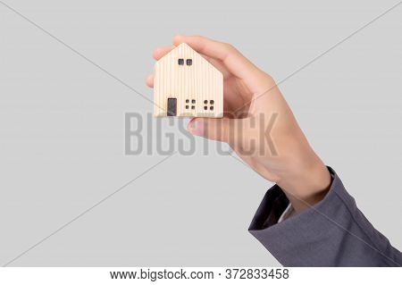 Hand Holding The Home Symbol Of Saving For Future, Insurance Agent And Credit, Ownership House, Debt