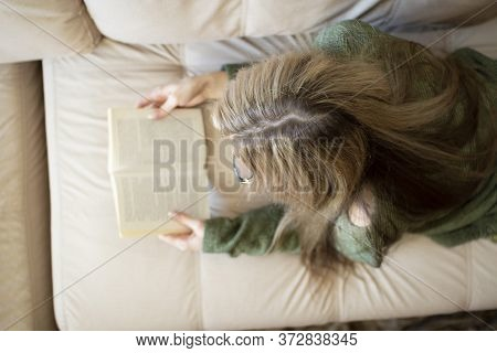 A Pretty Young Woman Is Happy To Read A Book At Home.