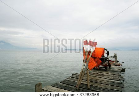 Oars and life jackets on jetty