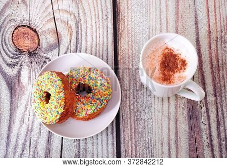 A Plate With Two Fresh Donuts In Multi-colored Sprinkles And A Mug Of Cappuccino With Cinnamon.