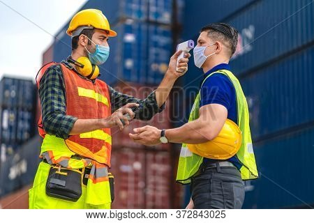 Professional Of Cargo Foreman In Helmets Standing And Using Infrared Thermometer For Checking Body T
