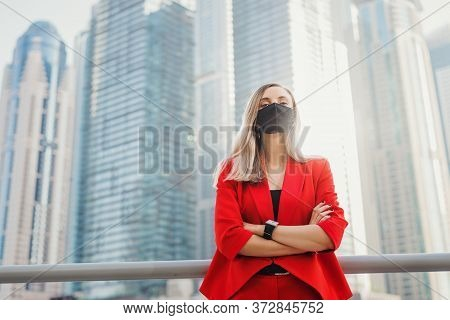 Young Businesswoman In Red Suit Wearing Reusable Face Mask Of Black Color Standing Near City Center